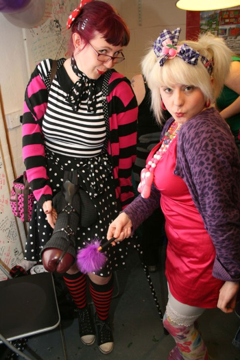 Two young women, dressed in a slightly punk and rockabilly style. The woman on the right has a large leather cuddly penis hanging from her belt loop; the other woman is pointing at it
