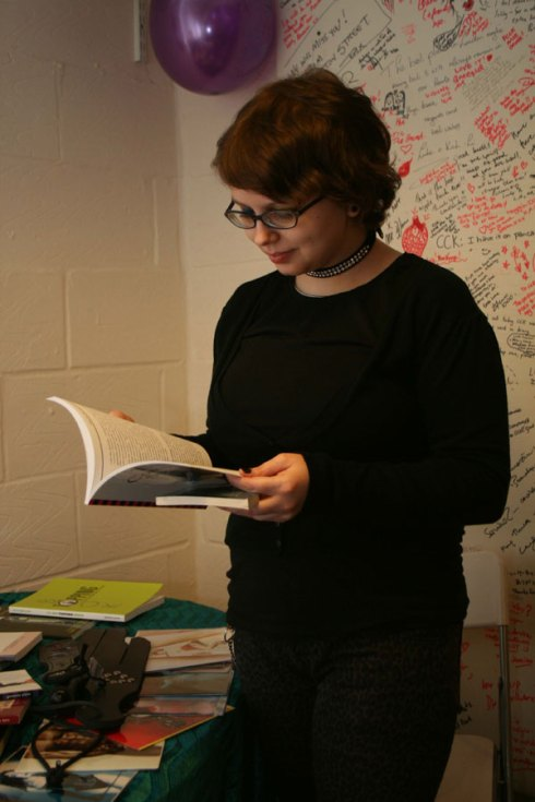 Young woman with short hair reading a book