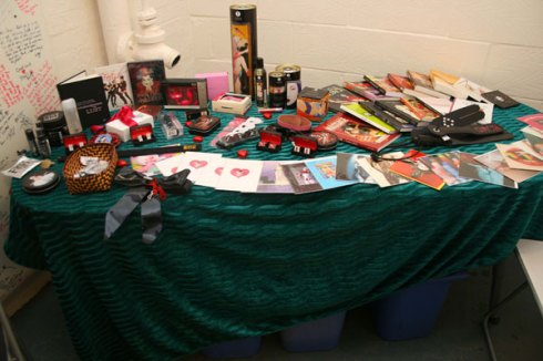 table, covered in green velvet, with a lot of books and sex toys spread out on it
