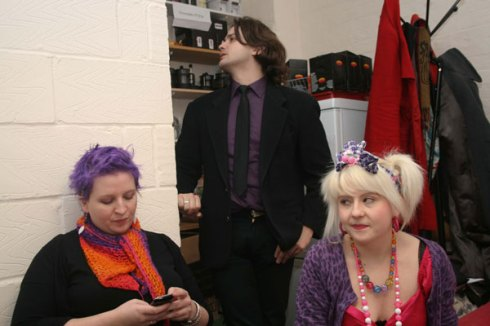 Two young women and a man; they are sitting down, he is standing behind them and looking away. The woman on the left has short hair, and is looking at her phone; the woman on the right has her hair in bunches and is smiling at the camera