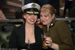 Two women. One is wearing a naval officer's jacket and hat, and is smiling at the camera. The other is wearing a military jacket and is holding a glass of wine