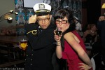 A man and a woman pose for the camera - she is wearing a fitted red dress, glasses, and is drinking from a glass of wine, one hand on her hip. He is wearing a naval officer's uniform and tipping his hat to the camera