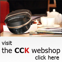 "hat sits next to a teapot and cup; underneath are the words ""visit the CCK webshop, click here"""